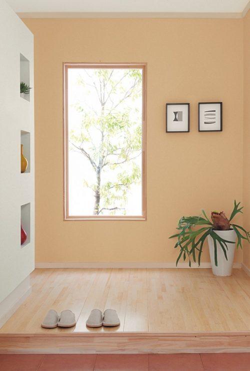 暖色系の壁紙で親しみやすさのある玄関